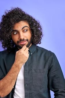 Nachdenklicher arabischer mann mit dem gelockten langen haar, das in der betrachtung steht und wegschaut, hand am kinn hält, lokalisiert über lila wand