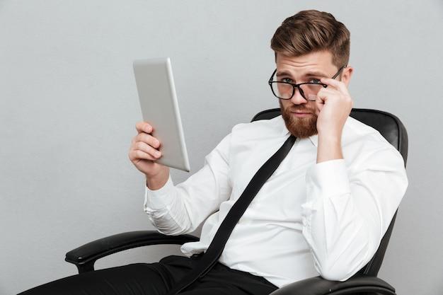 Nachdenklicher bärtiger geschäftsmann, der pc-tablette hält und über brillen schaut