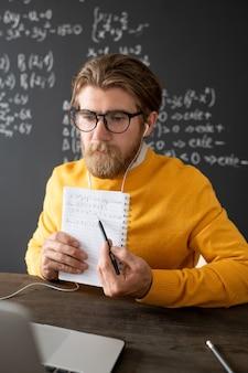 Nachdenklicher bärtiger lehrer in gelbem pullover, der an einen neuen vortrag vor dem laptop denkt, während er eine kurze pause zwischen den online-lektionen einlegt