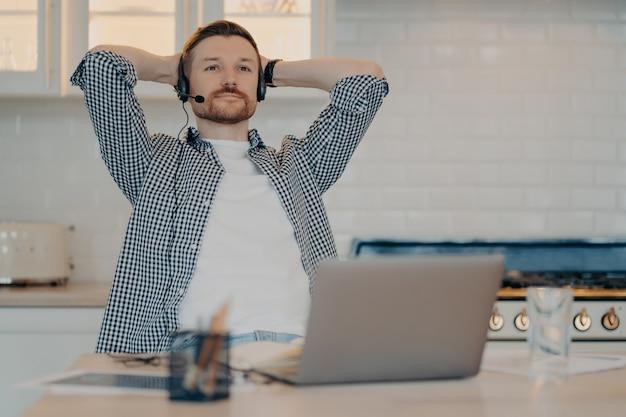 Nachdenklicher bärtiger männlicher freiberufler sitzt in entspannter pose macht pause, nachdem er online gearbeitet hat trägt headset mit mikrofon hört bildungswebinar bekommt fernunterricht nutzt neue computer-app