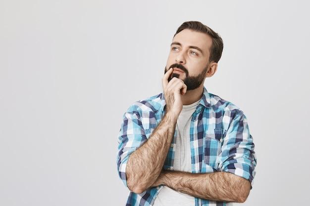 Nachdenklicher bärtiger mann denkt, trifft entscheidung