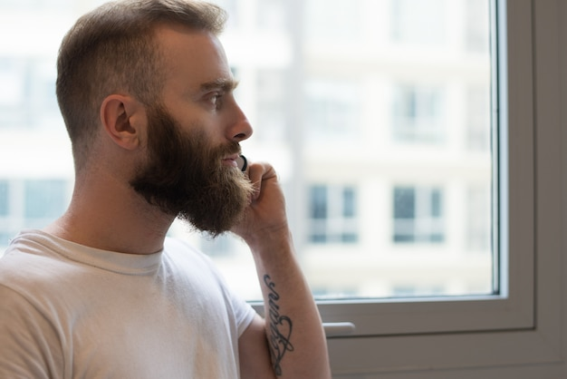 Nachdenklicher bärtiger mann, der am telefon spricht und heraus fenster schaut