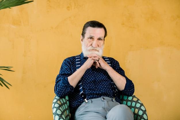 Nachdenklicher bärtiger mann, der kamera betrachtet, im stuhl sitzend. älterer mann in stilvoller kleidung, der von etwas träumt, in gedanken versunken. studioaufnahme auf gelbem hintergrund