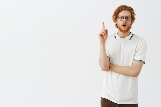 Nachdenklicher bärtiger rothaariger kerl, der mit brille gegen die weiße wand aufwirft
