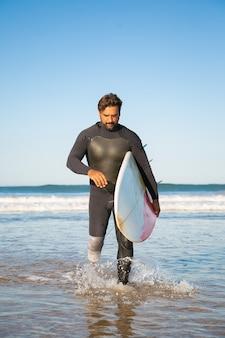 Nachdenklicher behinderter surfer, der im meerwasser mit brett geht