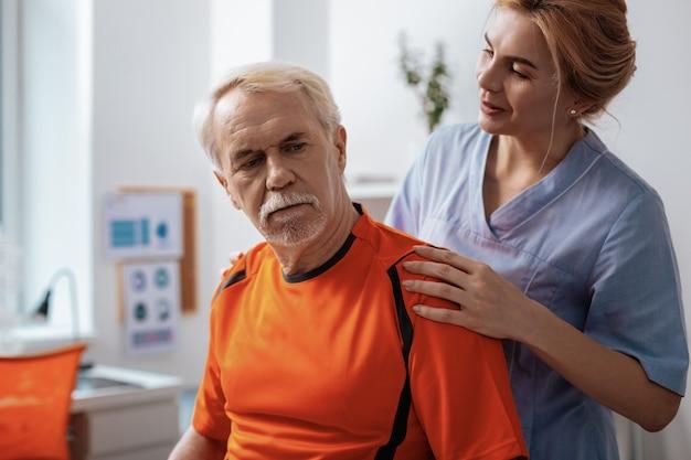 Nachdenklicher blick. angenehmer alter mann, der vor seiner krankenschwester sitzt und über seine gesundheit nachdenkt