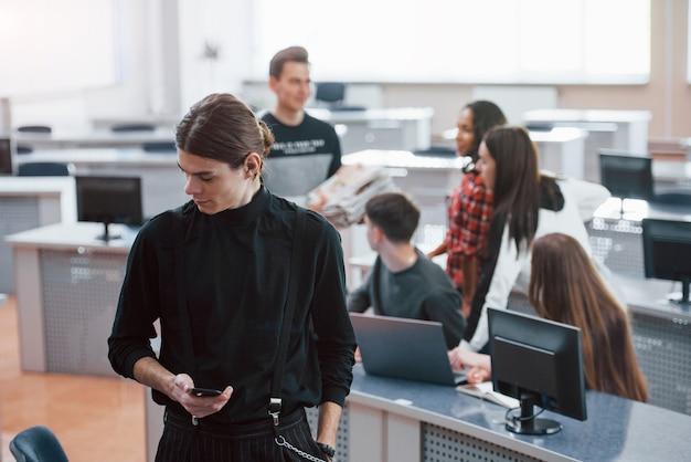 Nachdenklicher blick. gruppe junger leute in freizeitkleidung, die im modernen büro arbeiten