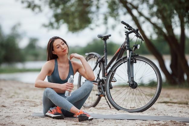 Nachdenklicher blick. weibliche radfahrerin mit guter körperform, die tagsüber nahe ihrem fahrrad am strand sitzt