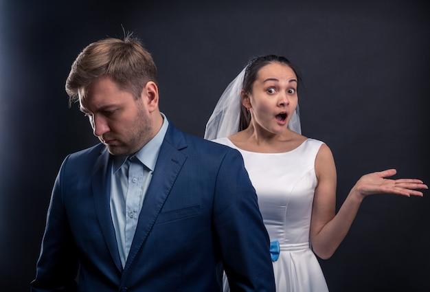 Nachdenklicher bräutigam und überraschtes brautstudiofoto