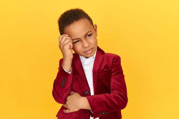 Nachdenklicher entzückender kleiner junge von afrikanischem aussehen, der nach oben schaut und hand auf seiner stirn hält, die nachdenklichen gesichtsausdruck hat und versucht, wichtige informationen zu sammeln.