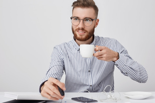 Nachdenklicher erfolgreicher junger männlicher geschäftsmann mit bart und trendiger frisur