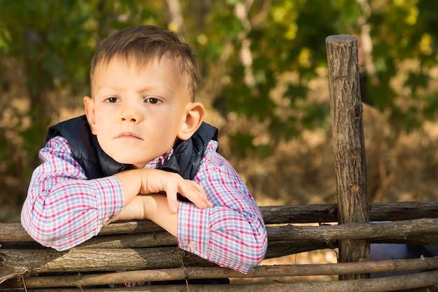 Nachdenklicher ernster junge, der sich im freien auf einen rustikalen holzzaun lehnt und mit einem stirnrunzeln zur seite der kamera starrt