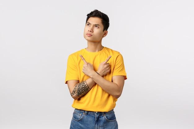 Nachdenklicher, ernsthaft aussehender junger asiatischer männlicher student, der überlegt, was die universität wählt, nachdenklich die stirn runzelt, nach oben schaut, seitwärts zeigt, links und rechts, zwei varianten oder auswahlmöglichkeiten, weiße wand denkt