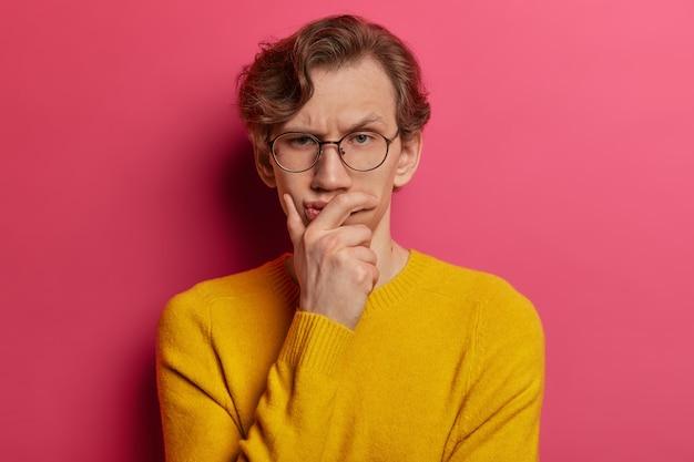 Nachdenklicher, ernsthaft aussehender mann runzelt die stirn und schaut direkt, hält das kinn, hat lästige gedanken, trägt eine brille und einen gelben pullover, hat einen verdächtigen ausdruck und sucht nach einer lösung