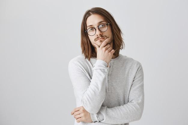Nachdenklicher ernsthafter mann denkt nach, trägt eine brille und trifft eine entscheidung