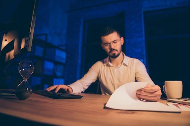 Nachdenklicher ernsthafter student, der nachts für prüfungen lernt