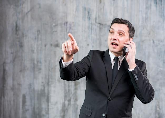 Nachdenklicher erwachsener geschäftsmann, der am telefon spricht