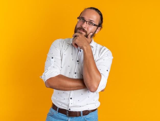 Nachdenklicher erwachsener gutaussehender mann mit brille, der die hand am kinn hält und die kamera isoliert auf orangefarbener wand mit kopienraum betrachtet