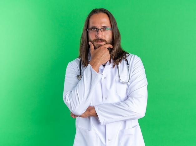 Nachdenklicher erwachsener männlicher arzt mit medizinischem gewand und stethoskop mit brille, der die hand am kinn hält und auf die kamera schaut, die auf grüner wand mit kopienraum isoliert ist