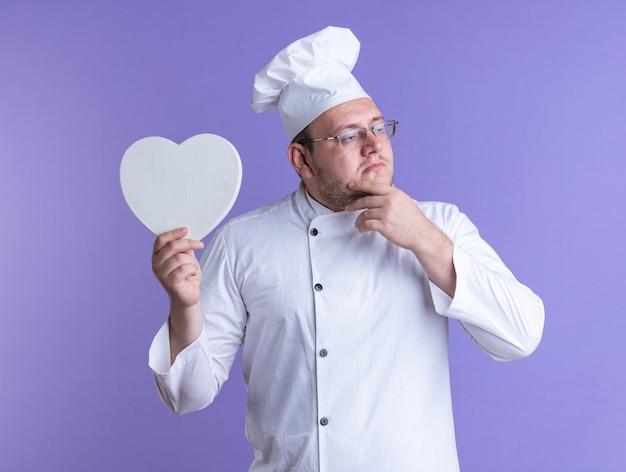 Nachdenklicher erwachsener männlicher koch, der kochuniform und brille trägt, isoliert auf dem halten der hand am kinn, das herzform mit blick auf die violette seitenwand hält