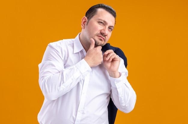 Nachdenklicher erwachsener slawischer geschäftsmann, der jacke auf seiner schulter hält und auf die seite schaut, die hand auf sein kinn legt