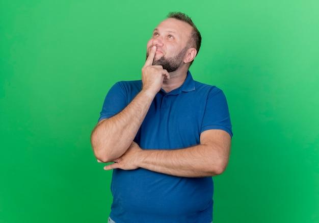 Nachdenklicher erwachsener slawischer mann, der hand unter ellbogen und finger auf lippen setzt, die lokal auf grüner wand mit kopienraum nach oben schauen