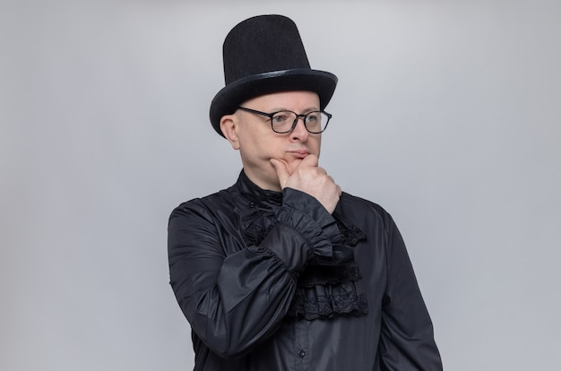 Nachdenklicher erwachsener slawischer mann mit hut und optischer brille in schwarzem gothic-hemd, der die hand auf sein kinn legt und zur seite schaut