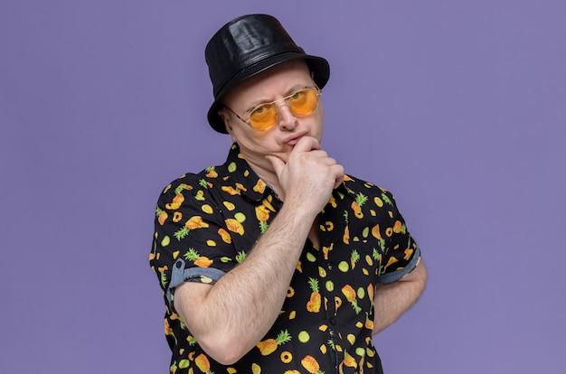 Nachdenklicher erwachsener slawischer mann mit schwarzem hut mit sonnenbrille, der die hand auf sein kinn legt und