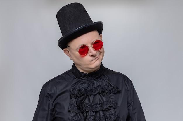 Nachdenklicher erwachsener slawischer mann mit zylinder und sonnenbrille in schwarzem gothic-hemd, der nach oben schaut