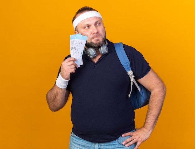Nachdenklicher erwachsener slawischer sportlicher mann mit kopfhörern, die rucksackstirnband und armbänder halten, die flugtickets halten und seite betrachten, die auf orange wand mit kopienraum isoliert ist