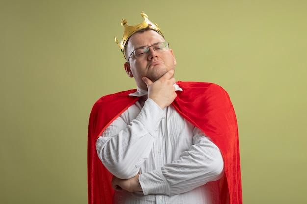 Nachdenklicher erwachsener slawischer superheldenmann im roten umhang, der brille und krone trägt und seite betrachtet, die kinn berührt, lokalisiert auf olivgrüner wand mit kopienraum
