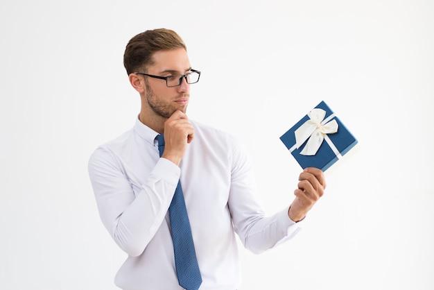 Nachdenklicher führender geschäftsmann, der geschenkbox mit bandbogen hält