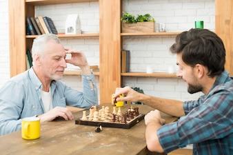 Nachdenklicher gealterter Mann und junger Kerl, die bei Tisch Schach im Raum spielen