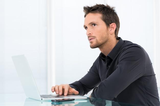 Nachdenklicher geschäftsmann, der am laptop arbeitet
