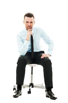 Nachdenklicher geschäftsmann, der auf stuhl sitzt