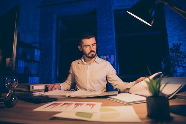 Nachdenklicher geschäftsmann, der bei einem beratungsunternehmen arbeitet, das berichte studiert