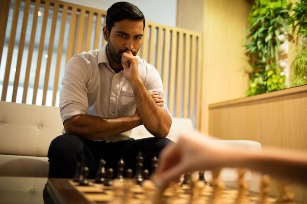 Nachdenklicher geschäftsmann, der schach mit kollegin spielt