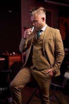 Nachdenklicher geschäftsmann im anzug, der drinnen im dunklen raum whisky trinkt