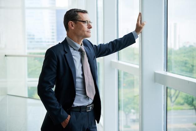 Nachdenklicher geschäftsmann im bürokorridor