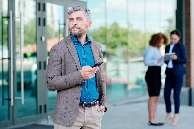 Nachdenklicher geschäftsmann mit smartphone, der überlegt, wohin er zum mittagessen gehen soll, während er mit zwei kollegen hinter dem bürogebäude steht