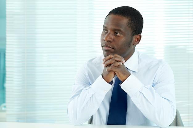 Nachdenklicher geschäftsmann sitzt in seinem büro