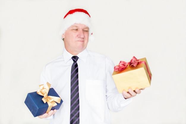 Nachdenklicher gesicht verziehender geschäftsmann, der geschenk wählt