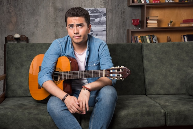 Nachdenklicher gitarrist, der eine schöne gitarre hält und auf sofa sitzt. hochwertiges foto