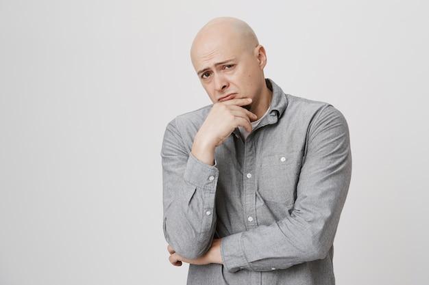Nachdenklicher glatzkopf denkt nach, trifft eine entscheidung