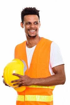 Nachdenklicher glücklicher afrikanischer mannbauarbeiter, der lächelt, während er sicherheitshelm hält