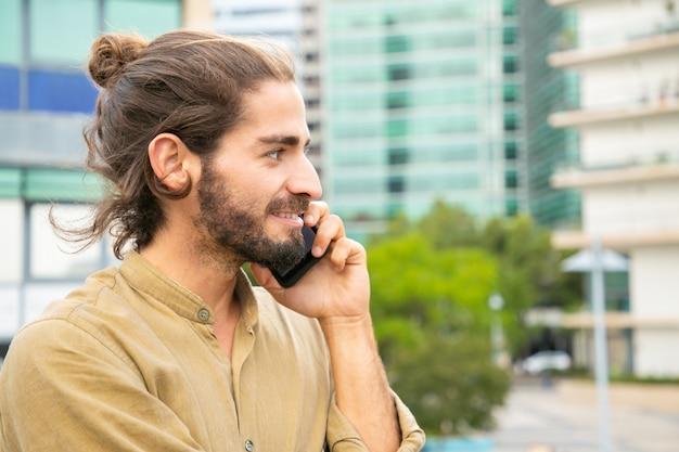 Nachdenklicher glücklicher hippie-kerl, der auf zelle spricht