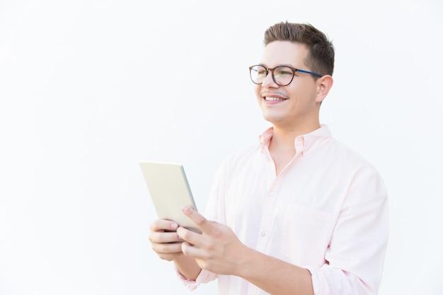 Nachdenklicher glücklicher kerl in den brillen, die tablette halten