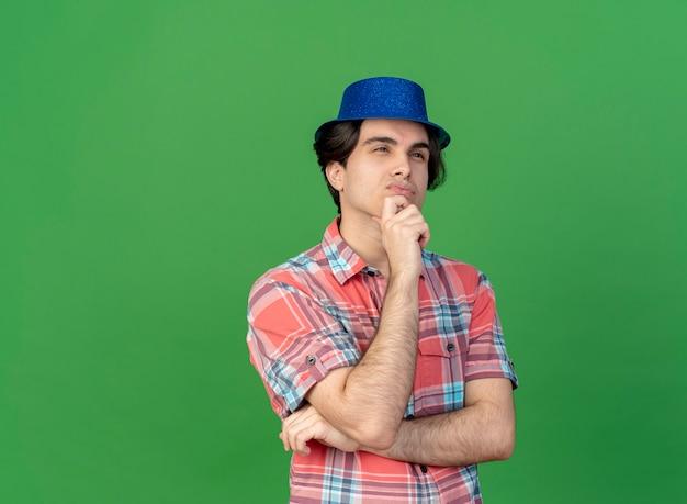 Nachdenklicher, gutaussehender kaukasischer mann mit blauem partyhut hält das kinn, das auf die seite schaut