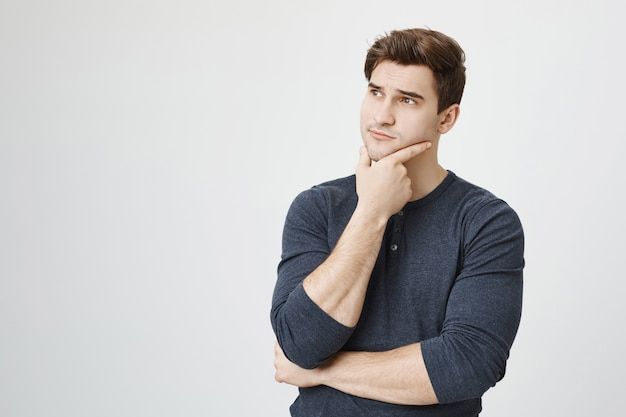 Nachdenklicher, gutaussehender männlicher student, der nachdenklich nach links schaut