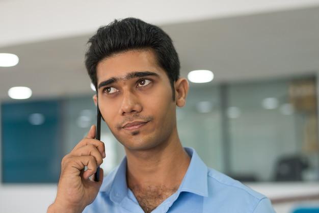 Nachdenklicher gutaussehender mann, der auf kunden am handy hört